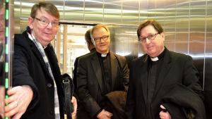 Kyrkoherdarna Stefan Forsén, Roger Rönnberg ochMartin Fagerudd står i en hiss.