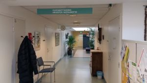 En korridor med en jacka på en hängare, en stol, en krukväxt och en skylt med texten Vuxenmottagning, på en psykiatrisk poliklinik.