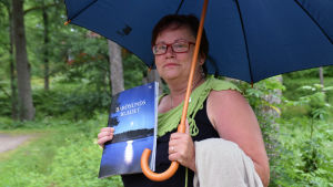 Margita Björklöf står och håller i ett paraply och ett exemplar av Barösundsbladet.