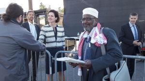 Mohamed Hagi Farah ser glad och nöjd ut, står med en lista i handen, Anna Kinberg Batra i bakgrunden