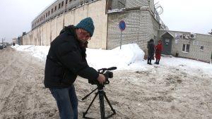 Ulkolinjan kuvaaja Serhi Lavor Penzan tutkintavankilan edessä kuvaamassa.