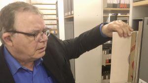 Paavo Annus tar fram en vinylskiva från hyllorna i ljudarkivet på Estlands nationalarkiv.