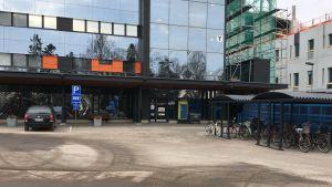 På långt håll syns dörren till infektionsmottagningen i sjukhuset. Bredvid syns byggställningar som hör till bygget av H-huset.