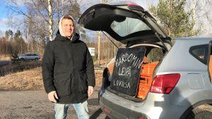En man vid sin bils baklucka. I bakluckan finns det en skylt där det står Hardomin leipä Loviisa.