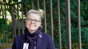 Susan Nymander tittar leende in i kameran framför en vägg av gröna buskar.