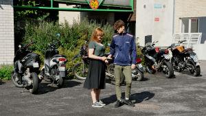 Saga Rosenlund och Christoffer Rönnholm står en bit bort från kameran, vid skolan intill en lång rad med skotrar och mopeder.