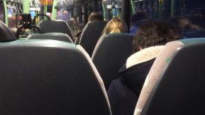 Bussinteriör, passagerare syns bakifrån.