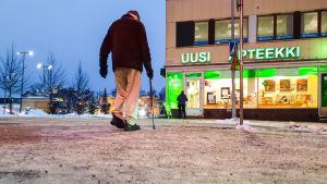 Äldre man går över gatan i Borgå centrum. Bilden är tagen nerifrån och man ser is, snö och sand på marken.