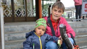 En medelålders kvinna sitter på huk bredvid ett barn. De befinner sig på en trappa utanför en matbutik. Båda tittar in i kameran.