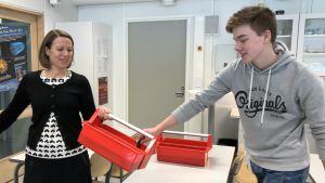 Studiehandledare Lotta Sundgren och Hamish Simpson som lägger sin mobiltelefon i en av Pargas Svenska Gymnasiums nya telefonlådor.