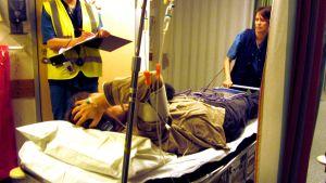 Patient på bår i sjukhuskorridor.