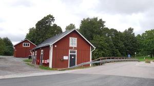 Små röda bodar längs ån i Ingå kyrkby.