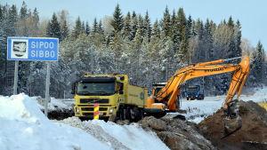 Vägarbete i vinterlandskap.
