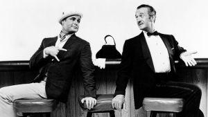 Freddy (Marlon Brando) och Lawrence (David Niven) sitter vid en bardisk och ser på varandra.