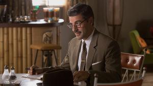 Bud Cooper (Oscar Isaac) sitter vid ett köksbord och ser finurlig ut.