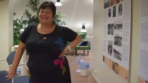 En kvinna i svart klänning ler mot kameran. Hon står i en utställningshall i ett bibliotek (Hangö)