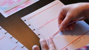 Ett vitt kalenderblad. Limmar ett rosa långt och smalt klistermärke mellan dagarna.