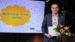 """Filip Saxén står iklädd kostym och håller i ett diplom och en blombukett. Till vänster syns en teveskärm där det står """"Miehen työ 2020""""."""