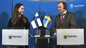 Sanna Marin och Stefan Löfven tittar på varandra under en presskonferens i Harpsund.