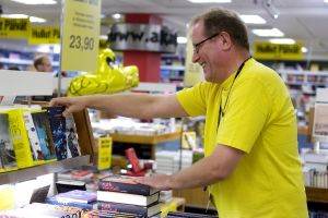 En försäljare organiserar reaböcker på Akademiska bokhandeln