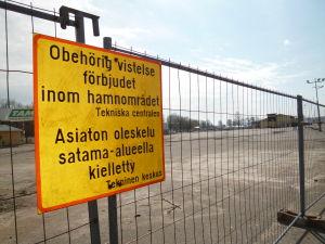 Ett staket med förbudstext: Obehörig vistelse förbjudet inom hamnområdet. Tekniska centralen.