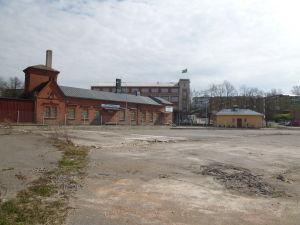 Sprucken asfaltplan med byggnader i bakgrunden.