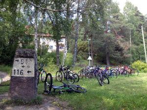 Cyklar utanför en byskola, grönt gräs, i förgrunden en gammal milstolpe.