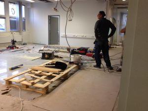Kontorslokal byggs om. verktyg och virke på golvet, elledningar hänger i taket, en arbetskarl står med ryggen till.