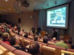 Publik i auditorium tittar på bilder som visas om en plan för Norra hamnen i Ekenäs.