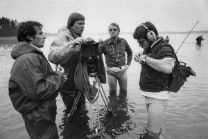 Ohjaaja Kalle Holmberg ja apulaisohjaaja Lauri Törhönen uimahousut jalassa. Kuvausryhmä seisoo järvessä polviaan myöten