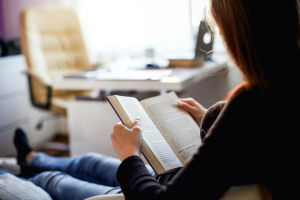 Kvinna läser bok på soffa.