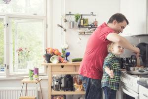 Isä ja lapsi kokkaavat yhdessä hellan vieressä.