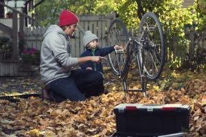 Isä ja lapsi korjaavat pyörää yhdessä. Syksyinen maisema, lehtiä maassa.