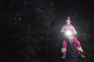 Lapsi istuu isän olkapäillä metsässä, yöinen maisema - isällä otsalamppu.