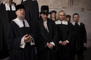 1600-luvun hoviherrat seisovat rivissä mustissa vaatteissaan.