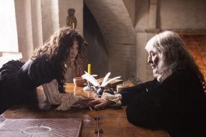 Kuningatar Kristiina nojaa pöydän yli filosofi Descartesin puoleen.