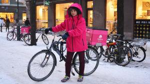 Bild på Anton Salmenkylä i rosa jacka och hans cykel med en rosa termobox bakpå.