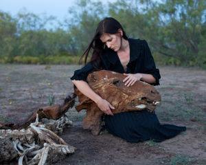 Nainen pitää kuolleen hevosen päätä sylissään
