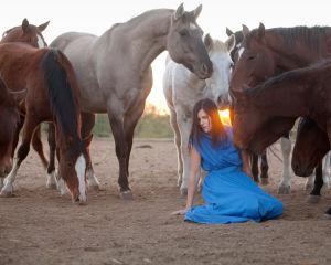 Nainen istuu hevosten keskellä