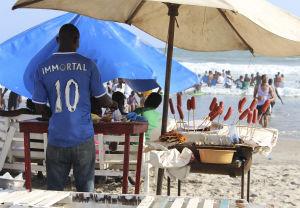 Mies grillaa rannalla Accrassa, Ghanassa, makkarat odottavat tikuissaan pystyssä