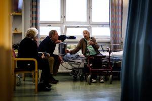 Tre personer sitter i sjukhusrum.