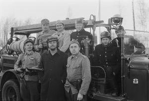 Ylhäällä vasemmalla Erkki Pajala ja Kari Franck. Edessä Vesa Mäkelä, ohjaaja Veli-Matti Saikkonen ja Esko Hukkanen sekä avustajina palokuntalaisia.