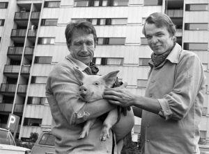 Keittiömestarit Veijo Vanamo ja Jaakko Kolmonen porsas sylissään kerrostalon pihamaalla (1970)