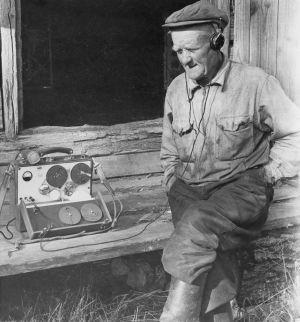 Radiotyö. Kaarle Nordenstrengin radio-ohjelma Ritarin talosta. Maanviljelijä Otto  Ritari kuuntelee kuulokkeilla nauhoituksen tulosta riihen ovella maatilallaan. Maihak- äänityslaite, maihakki. Yleisradion ohjelmat.