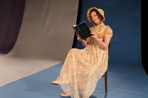 Kuvassa kirjaa lukeva nainen