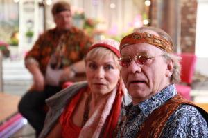 Ainon kahvilan 60-luku bileissä Aino ja Ensio pukeutuneena hipeiksi. Taustalla mies.