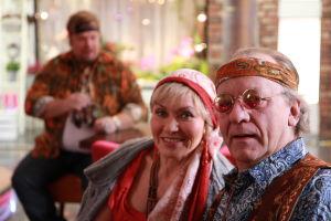 Ainon kahvilan 60-luku bileissä Aino ja Ensio pukeutuneena hipeiksi. Taustalla mies istuu.