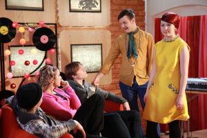 Ainon kahvilan 60-luku bileissä Aapo, Emmi, Tomi, Krista ja Karri. Emmi ja Aapo seisovat, muut istuvat sohvalla.