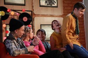 Ainon kahvilan 60-luku bileissä Aapo istuu Emmin sylissä. Emmi istuu Tomin sylissä. Emmi nauraa.