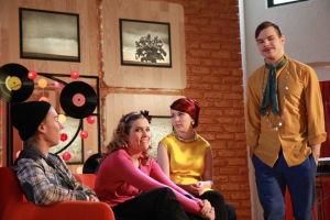 Ainon kahvilan 60-luku bileissä Aapo seisoo. Karri, Krista ja Emmi istuvat sohvalla.